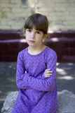 Angry girl seven years old wearing blue dress. Sitting on bench in the streeta stock photo