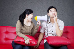 Angry girl shout at boyfriend on red sofa Royalty Free Stock Images