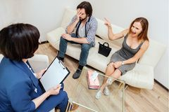 Angry girl is sitting on sofa with her husband. She is looking on therapist but screaming and pointing on man. Angry girl is sitting on sofa with her husband Stock Photo