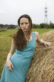 Angry girl standing near haystack Stock Image