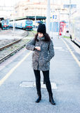 Angry girl waiting for her train to arrive at the railway station. Looking constantly her watch stock photography