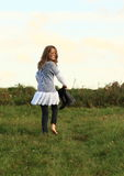 Angry girl walking barefoot. Little barefoot girl - angry kid walking on meadow with boots in hand Stock Image