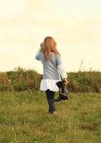 Angry girl walking barefoot. Little barefoot girl - angry kid walking on meadow with boots in hand Royalty Free Stock Images