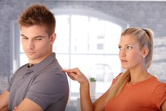 Angry girlfriend poking boyfriend. Angry girlfriend poking shoulder of boyfriend with finger looking upset royalty free stock images