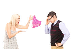 Angry girlfriend shouting at her boyfriend. And holding female knickers isolated on white background royalty free stock images
