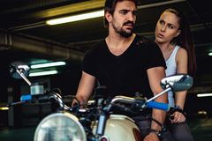 Angry girlfriend talking to her biker boyfriend in a garage. While riding a motorcycle royalty free stock images