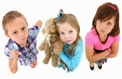 Angry Girls. Adorable group of angry 7 year old girls over white background looking up towards camera.  Top view over white background Royalty Free Stock Photo