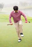 Angry golfer trying to brake his club. At the golf course Stock Photo