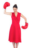 Angry gorgeous brunette in red dress wearing boxing gloves Royalty Free Stock Image