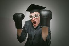 Graduate student. Angry graduate student in the boxing gloves isolated on gray background. Education concept. A protection of diploma work stock image