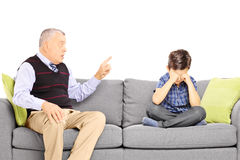 Angry grandad shouting at his nephew, seated on a sofa. Isolated on white background Stock Photos