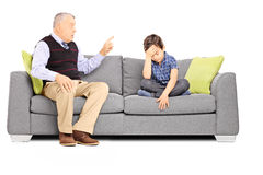 Angry granddad shouting at his sad nephew, seated on a sofa. Isolated on white background Royalty Free Stock Photo