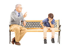 Angry grandfather shouting at his sad nephew, seated on a bench. Angry grandfather shouting at his sad nephew, seated on a wooden bench, isolated on white Royalty Free Stock Photo