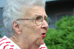 Angry Grandmother. Portrait in 3/4 profile of grandmother figure with an angry expression royalty free stock image