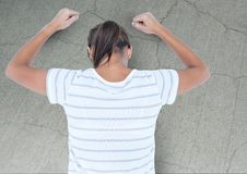 Angry grief struck young woman banging wall with cracks. Digital composite of Angry grief struck young woman banging wall with cracks Royalty Free Stock Images