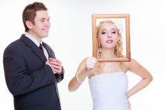 Angry groom and bride holding empty frame Royalty Free Stock Photography