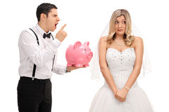 Angry groom holding a piggybank and scolding an embarrassed brid Stock Photo