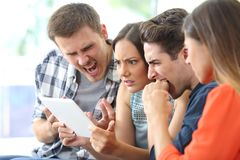 Angry group of friends watching media on tablet. Sitting on a couch in the living room at home royalty free stock photo