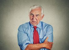 Angry grumpy pissed off senior mature man. Portrait of unhappy grumpy pissed off senior mature man isolated on gray wall background. Negative human emotions Stock Photo