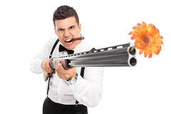 Angry guy shooting flowers from a rifle Royalty Free Stock Photos