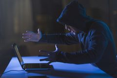 Angry hacker with laptop computer in dark room Royalty Free Stock Photos