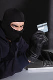 Angry hacker using credit card and laptop Stock Photos