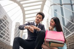 Angry boyfriend blame girlfriend for late. Angry handsome businessman boyfriend look at watch to blaim his girlfriend to miss appointment time due to shopping Stock Images