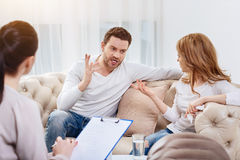 Angry handsome man disagreeing with his wife. Mutual misunderstanding. Angry emotional handsome men holding his hand up and saying something to his wife while Stock Images