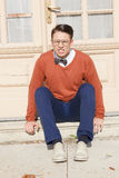 Angry  handsome man with glasses and sweater sitting on steps in. Front of house and posing  while looking at camera, vintage retro fashion  photo Royalty Free Stock Photo