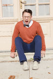 Angry  handsome man with glasses and sweater sitting on steps in. Angry  man with open mouth with glasses and sweater sitting on steps in front of house and Royalty Free Stock Images