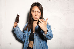 Angry hipster woman eating chocolate showing middle finger. Picture of young angry hipster woman standing over gray background eating chocolate showing middle stock photo