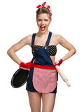 Angry housewife with battledore and black frying pan Royalty Free Stock Image