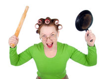 Angry housewife in hair rollers is holding Stock Photos