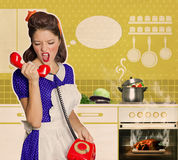 Angry housewife shouting on the phone in the kitchen Royalty Free Stock Photos