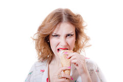 Angry or hungry pretty girl eating ice cream cone looking at camera isolated on white background Royalty Free Stock Photo