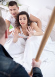 Angry husband with baseball bat caught cheating wife with lover Royalty Free Stock Photos