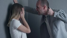 Angry husband trying to hit his wife indoors. Concept of domestic violence