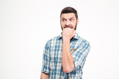 Angry irritated aggressive young bearded man biting his fist Royalty Free Stock Image