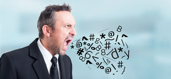 Angry irritated businessman screaming and shouting out loud. With symbols and letters coming out of his mouth as insulting concept Stock Photos