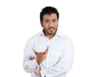 Angry irritated young man placing out his hand as if to ask, whats your problem or what are you saying? Royalty Free Stock Images