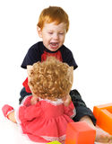 Angry kid with a doll Royalty Free Stock Image