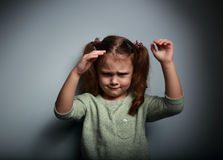 Angry kid girl moving the hands on dark Stock Photos