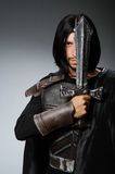 Angry knight with sword against. Dark background Royalty Free Stock Images