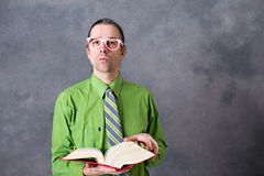 Angry lawyer with statute book and pink glasses. Angry lawyer in green shirt and necktie with statute book and pink glasses Royalty Free Stock Image