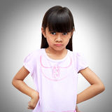 Angry little asian girl. On a grey background Royalty Free Stock Photos