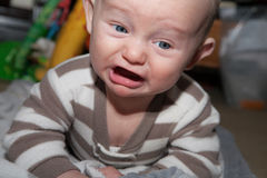 Angry Little Baby. Baby with blue eyes crying and angry disgusted expression up close Stock Images