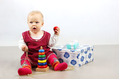 Angry little baby girl sitting alone with presents and toys. Stock Photography