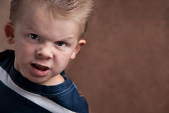 Angry little boy glaring at the camera. On a brown textured background stock photos