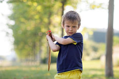 Angry little boy, holding sword, glaring with a mad face at the. Camera, outdoors in the park stock photo
