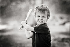 Angry little boy, holding sword, glaring with a mad face at the. Camera, outdoors in the park, monochrome conversion royalty free stock photos